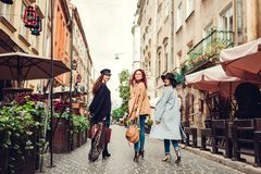 Outdoor shot of three young women walking on city street. Girls turning and looking at camera. Ladies having fun royalty free stock images