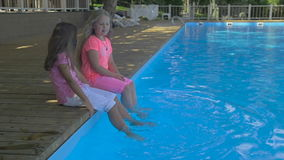 Outdoor shot of two little girls dipping their feet in the pool. Cute little girls sitting on the edge of a swimming. Pool on a sunny day stock video
