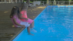 Outdoor shot of two little girls dipping their feet in the pool. Cute little girls sitting on the edge of a swimming. Pool on a sunny day stock video footage