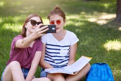 Outdoor shot of two young beautiful females sitting on grass in lotus position, makes selfie in park, wears in t shirts and shorts stock photo