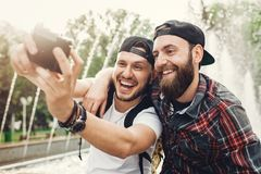 Outdoor shot of two young men having fun on public park and taking selfie. Two handsome bearded friends enjoying a day in park. royalty free stock photo