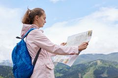 Outdoor shot of young caucasian female with blue backpack and map on hill above mountains and forests, hikers looking at map and. Try to find way, taking part royalty free stock photography