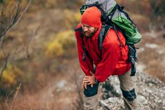 Outdoor shot of young male hiking in mountains wearing red clothes exploring new place. Traveler bearded man trekking. And mountaineering during his journey stock image
