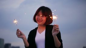 Outdoor shot of young people at rooftop party. Happy asian women enjoy and play sparkler at roof top party. Outdoor shot of young people at rooftop party. Happy stock footage