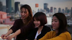 Outdoor shot of young people at rooftop party. Happy group of asia girl friends enjoy and play sparkler at roof top party. Outdoor shot of young people at stock footage