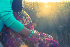 Outdoor shot of young pregnant woman in colorful dress Stock Image