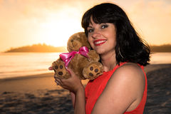 Outdoor shot of young pregnant woman in red dress hugging her baby toy Stock Photos