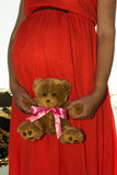 Outdoor shot of young pregnant woman in red dress standing with toy for her expected child and looking into the ocean Stock Images