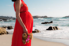 Outdoor shot of young pregnant woman in red dress standing with toy for her expected child and looking into the ocean Stock Photo