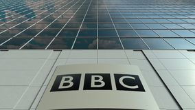 Signage board with British Broadcasting Corporation BBC logo. Modern office building facade time lapse. Editorial 3D