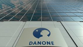 Signage board with Danone logo. Modern office building facade time lapse. Editorial 3D rendering