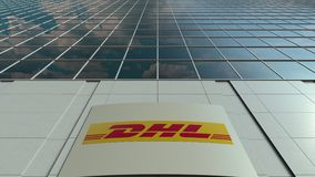 Signage board with DHL Express logo. Modern office building facade time lapse. Editorial 3D rendering
