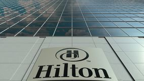 Signage board with Hilton Hotels Resorts logo. Modern office building facade time lapse. Editorial 3D rendering