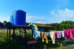 Outdoor simple blue plastic cistern and hut and clothes drying Royalty Free Stock Image