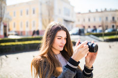 Outdoor smiling lifestyle portrait of pretty young woman having fun in the city in Europe with camera travel photo of photographer. Outdoor summer smiling Royalty Free Stock Photography