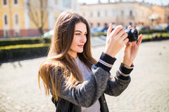 Outdoor smiling lifestyle portrait of pretty young woman having fun in the city in Europe with camera travel photo of photographer. Outdoor summer smiling Royalty Free Stock Photo