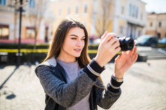 Outdoor smiling lifestyle portrait of pretty young woman having fun in the city in Europe with camera travel photo of photographer. Outdoor summer smiling Stock Images