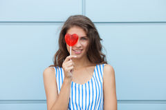 Outdoor smiling portrait of happy young beautiful brunette woman in striped summer dress posing with red heart lollipop against me Stock Images