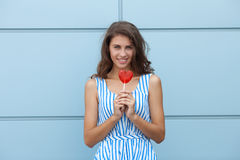 Outdoor smiling portrait of happy young beautiful brunette woman in striped summer dress posing with red heart lollipop against me Royalty Free Stock Photography