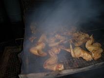 Outdoor smoky marinated chicken BBQ. Outdoor smoky chicken BBQ with deep homemade marinated mixture stock image