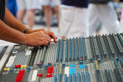 Outdoor Sound Mixing Board. Two hands working a sound board.  It is outside at a live performance.  There are people visible in the blurred background.  It uses Stock Images