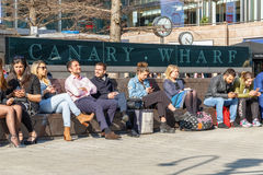 Outdoor space in Canary Wharf packed with people sitting and enj Royalty Free Stock Photo