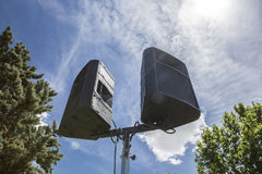 Outdoor speakers over leaf and blue cloudy sky Stock Photos