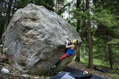 Outdoor sport activity. Rock climber girl . Outdoor sport activity. Rock climber girl ascending a challenging boulder rock. Woman in extreme sport climbing Stock Images