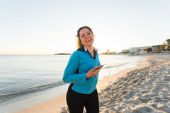 Outdoor sport, fitness gadget and people concept - Smiling female fitness holding smartphone with earphones. royalty free stock photos