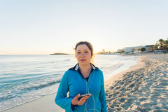 Outdoor sport, fitness gadget and people concept - Smiling female fitness holding smartphone with earphones. royalty free stock images