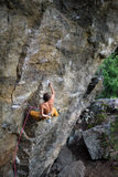 Outdoor sport. Rock climber dangles in midair as he struggles to climb a challenging cliff. Royalty Free Stock Images