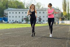Outdoor sports and fitness family. Sporty mature mother and teen daughter. Woman and girl are running around in the city stadium stock photos