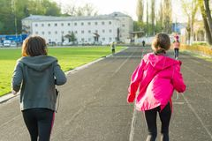Outdoor sports and fitness family. Sporty mature mother and teen daughter. Woman and girl are running around in the city stadium. Back view royalty free stock image