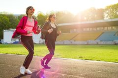 Sporty mature mother and teen daughter. Woman and girl are running around in the city stadium. Stock Image