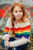 Outdoor spring portrait of adorable redheaded kid girl holding transparent umbrella. Wearing rainbow pullover, child playing outside on a rainy day, fashion Stock Photos