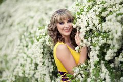 Outdoor spring portrait of a beautiful woman. Attractive girl in white flowers. Outdoor spring portrait of a smiling beautiful brown curly hair woman. Attractive Royalty Free Stock Photos