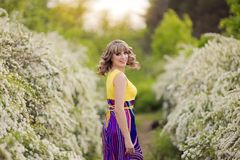 Outdoor spring portrait of a beautiful woman. Attractive girl in white flowers. Outdoor spring portrait of a smiling beautiful brown curly hair woman. Attractive Royalty Free Stock Photography