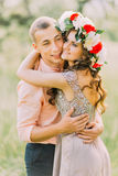 Outdoor spring portrait of young romantic hipster couple hugs  posing, in the city garden around blooming trees and flowers Royalty Free Stock Photo