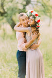 Outdoor spring portrait of young romantic hipster couple hugs  posing, in the city garden around blooming trees and flowers Stock Photos