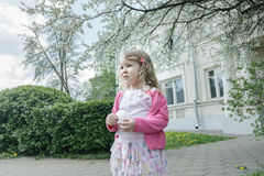 Outdoor springtime reverie portrait of little curly blonde at flowering fruit tree and porch background Royalty Free Stock Photo