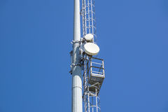 Outdoor stadium lights and telecommunication tower against daytime blue sky. Single row of bulbs with cell phone gsm antennas on tall metal pole. Room for text Stock Image