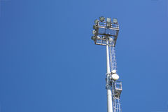 Outdoor stadium lights and telecommunication tower against daytime blue sky. Single row of bulbs with cell phone gsm antennas on tall metal pole. Room for text Royalty Free Stock Photos