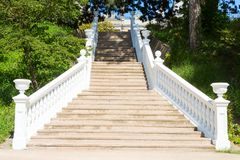 Outdoor staircase with white handrails. Outdoor stone staircase with the white handrails royalty free stock photos