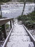 Outdoor stairway covered in snow down to river. Stairway covered in snow down to the Sandy River with handrail and littered with twigs and dead leaves Stock Images