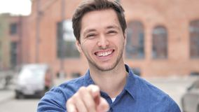 Outdoor Standing Young Man Pointing with Finger toward Camera. 4k high quality, 4k high quality stock video footage