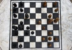 Outdoor stone chessboard with black and yellow figures top view. Competition and strategy concept. Defeat and fight concept. Chess wooden pieces on board royalty free stock images