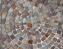 Outdoor stone flooring of porphyry cubes made with a round design, with circles that becomes larger starting from the center.  stock image