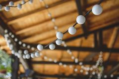 outdoor string lights hanging on a line with under a wooden roof. Royalty Free Stock Image