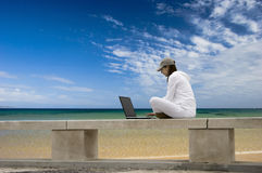 Outdoor study. Woman working with a laptop sitting in a wall with a great view over a beautiful green meadow Royalty Free Stock Image