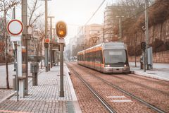 Metro train outdoors at city stop. Outdoor subway stop with modern futuristic glossy metro train or tram on railway track stretching to vanishing point, traffic Stock Photography